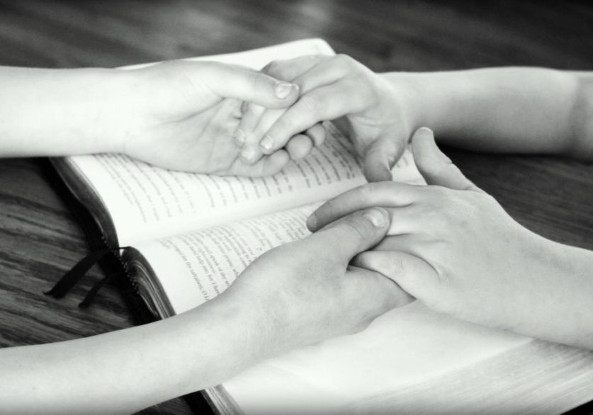 holding hands and reading the bible